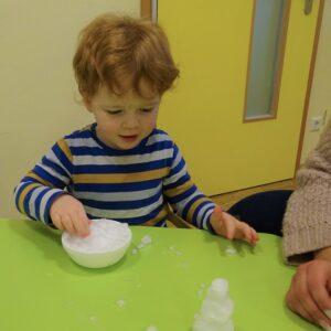 """Aktuelles """"Wintereinbruch"""" - Kind spielt mit Schnee innen"""
