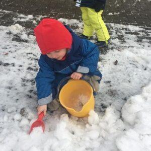 """Aktuelles """"Wintereinbruch"""" - Kind beim Schnee einsammeln mit einem Eimer"""