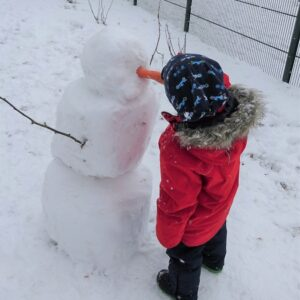 """Aktuelles """"Wintereinbruch"""" - Kind beim Schneemann bauen"""