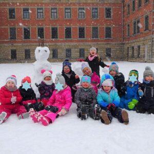 """Aktuelles """"Wintereinbruch"""" - Gruppenbild von Kindern mit Schneemann"""
