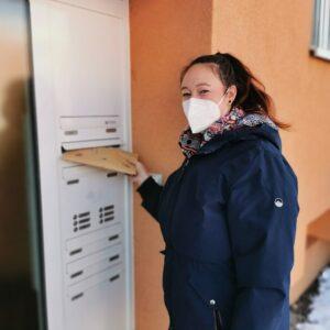 """Aktuelles """"Faschingspost"""" - Frau wirft ein Paket in den Briefkasten"""