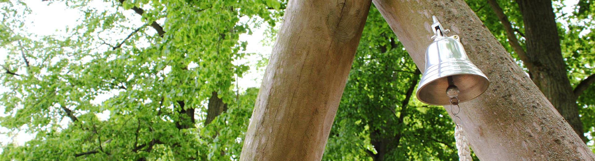 Metallglocke draußen an einem Holzstamm