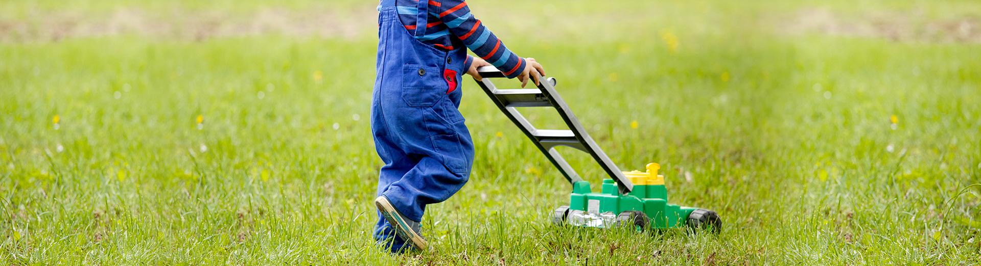 Kind schiebt einen Spielzeugrasenmäher über die Wiese