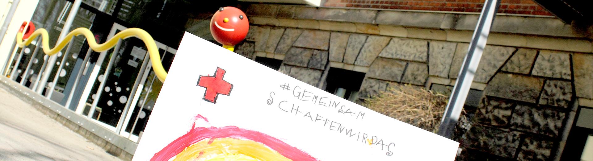 """Regenbogen mit dem Text """"#Gemeinsamschaffenwirdas"""" vor dem BRK-Kinderhaus Eingang"""