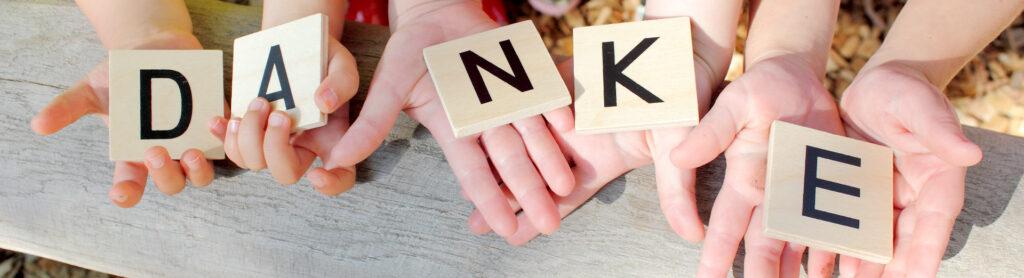 """Kinder halten Holzquadrate in den Händen mit dem Wort """"Danke"""""""