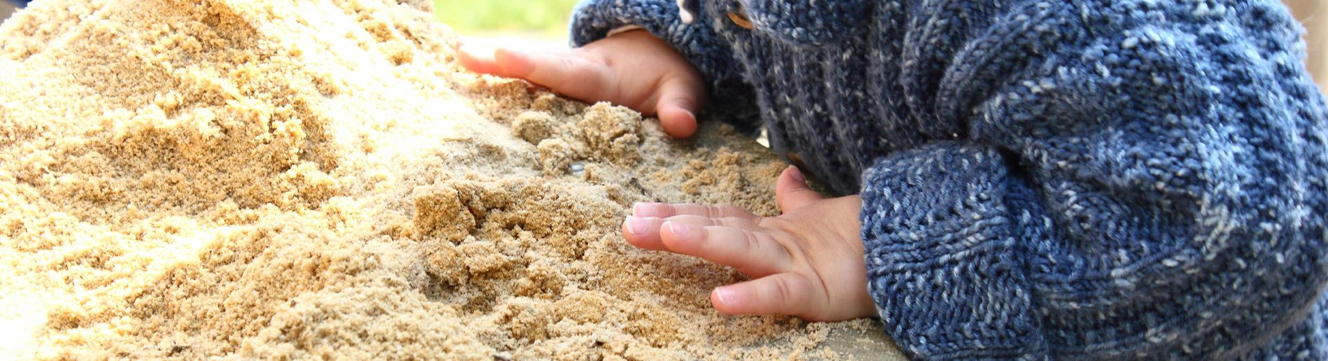 Kleine Kinderhände spielen im Sand