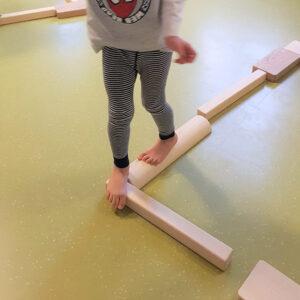 Kind balanciert über Holzbalken und -blöcke