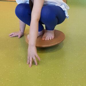 Kind hockt auf einem Gleichgewichtsboard