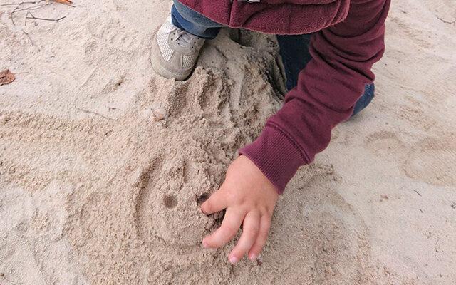 Kind malt ein Gesicht in den Sand
