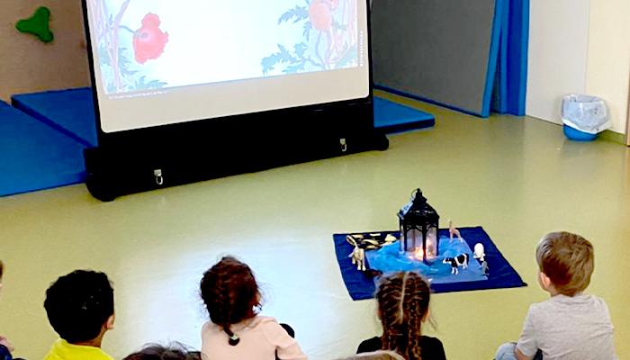 Kinder sitzen vor einer Leinwand als Bilderbuchkino