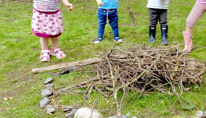 Kinder drauße von einem Holzhaufen
