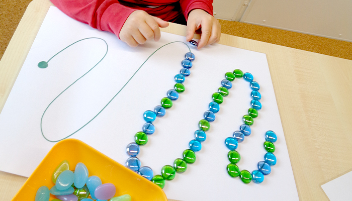 Kind legt Glasperlen auf eine aufgezeichnete Linie