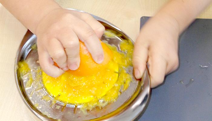 Kind quetscht Saft aus einer Orange
