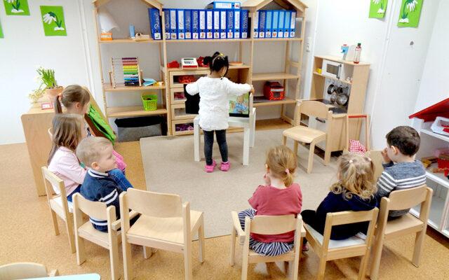 Sitzkreis Kinder mit dem Blick auf das Kamishibai was ein Mädchen aufstellt