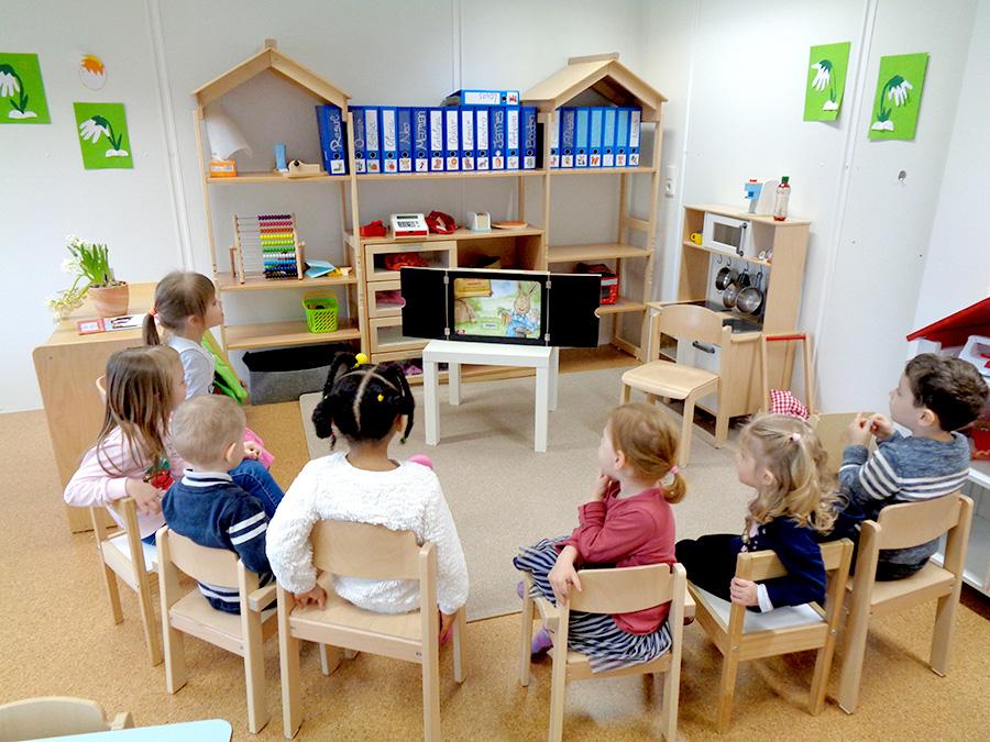 Sitzkreis Kinder mit dem Blick auf das Kamishibai