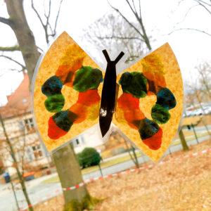 Bunter, gebastelter Schmetterling an der Scheibe