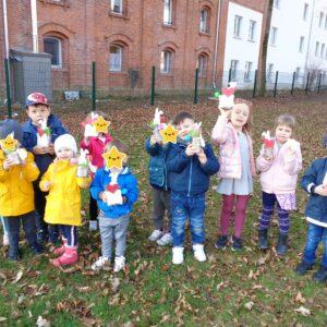 Kindergartengruppe steht auf einer Wiese und halten ihr Osternest in die Kamera. Alle lachen dabei