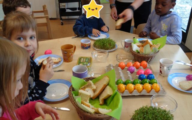 Die Kinder sitzen am Tisch und essen Brot mit Kresse und bunte Ostereier