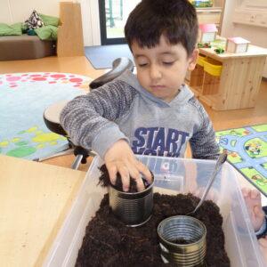 Kleiner Junge mit dunklen Haaren, bepflanzt sein Osternest mit Grassamen