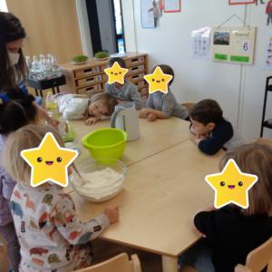 Die Kindergartenkinder backen einen Kuchen