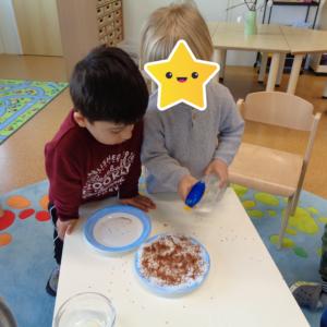 Zwei Jungs besprühen die Kresse Samen mit Wasser