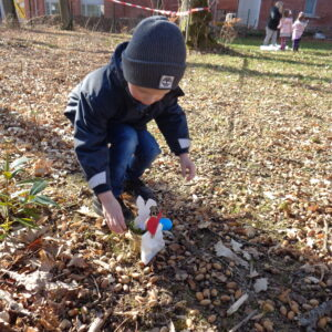 Junge findet Osternest im Garten