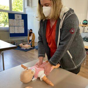 Eine Frau übt die Herzdruckmassage an einer Babypuppe.