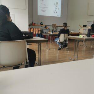 Teilnehmerinnen sitzen in einem Seminarraum.