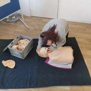 Eine Frau übt Wiederbelebungsmaßnahmen an einer Puppe.