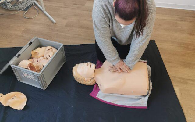 Eine Frau übt die Herzdruckmassage an einer Puppe.
