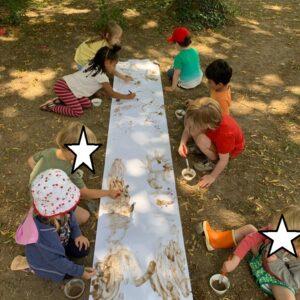 Kinder malen mit Erdfarbe auf ein Papier
