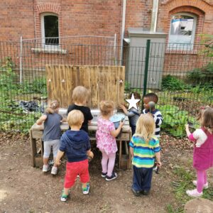 Die Kinder spielen an der Matschküche